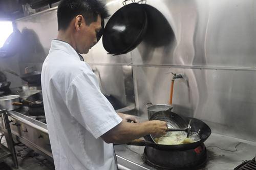 张厨师正在以拉油方式,来衡量羊肉的熟度。