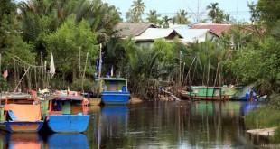 裕南小镇依河畔而建,渔民捕鱼归来渔船停靠河岸旁。