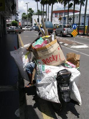 这位廋小的阿姨,忙完后,启动摩托车载着纸皮等回收资源回家去。