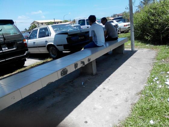 一中学校园外的巴士候车亭的非法小贩,把货品藏起来,令市局执法官员也无奈。